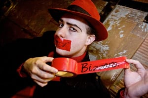 Bizzaro holding a roll of red duct tape, pulling out one end with his name written on it. He has a piece of tape over his mouth with a smile on it.